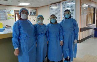 Four people stand in a hospital in full personal protective equipment (PPE)