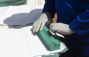 A long bar of green soap that can be cut into smaller bars is wrapped up to be distributed.