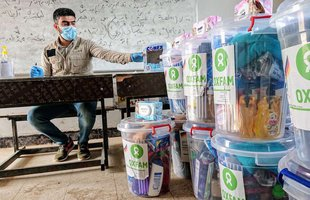 A man wears a mask and sits at a desk next to stacked clear buckets containing hygiene essentials like toothbrushes