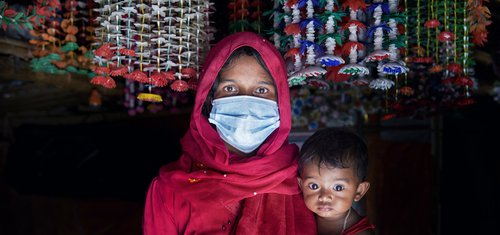 A woman wears a surgical mask and holds her baby in the Cox's Bazar refugee camp