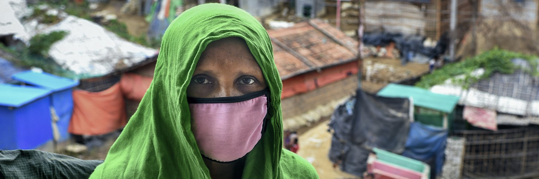 A woman wearing a pink facemask and green head scarf stands outside in a refugee camp in Bangladesh