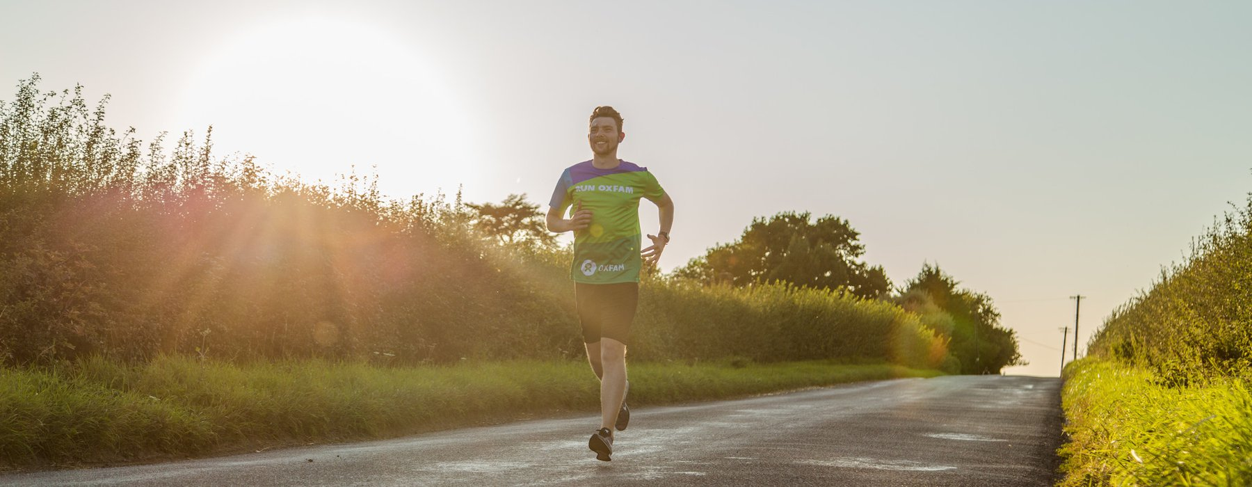 Runner Olly wearing Oxfam shirt training on road by fields.