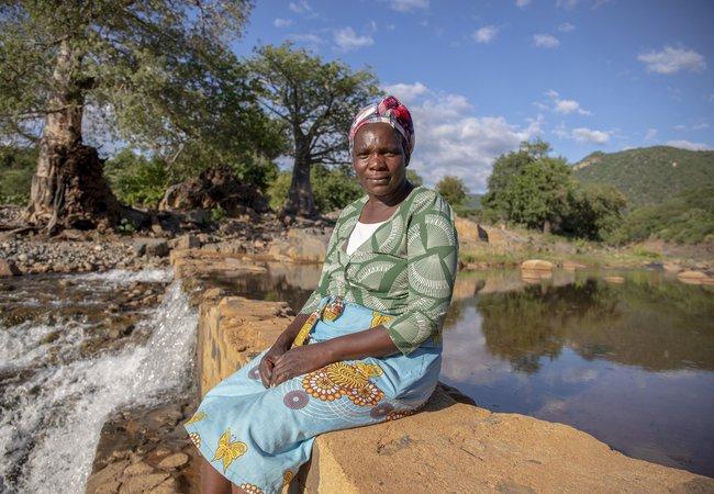 Sarah sits by the water at Nyanyadzi river, Chimanimani, Zimbabwe