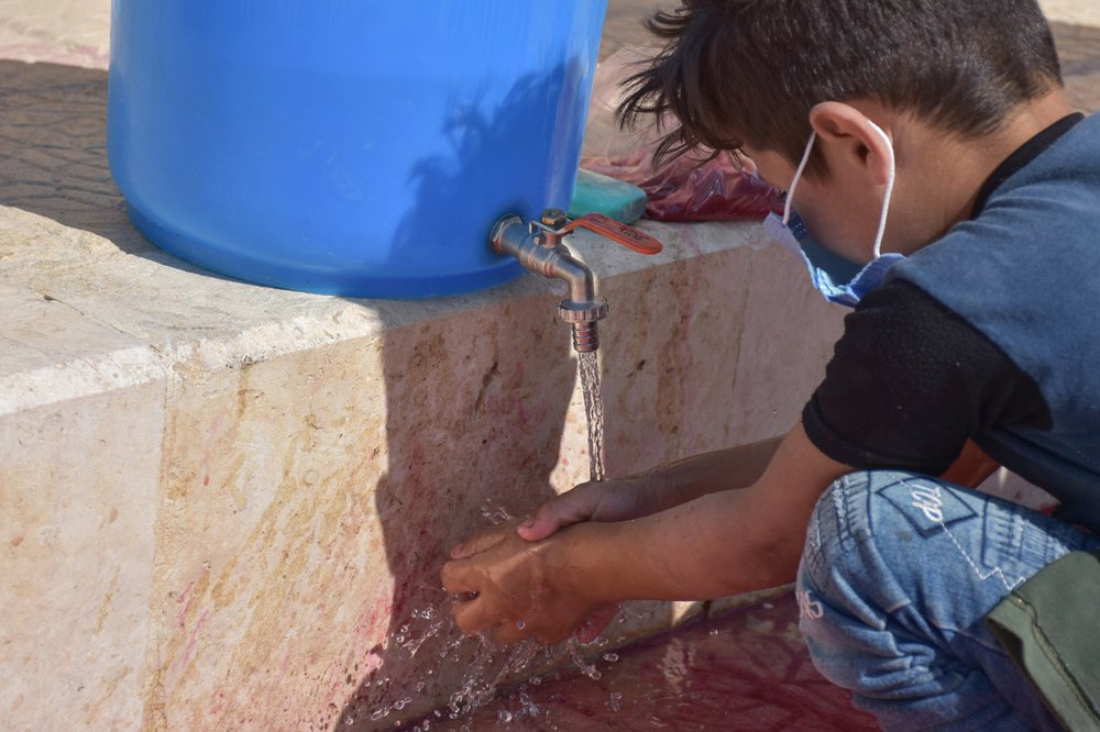 An eight-year-old boy wearing a face mask washes his hands under a tap.