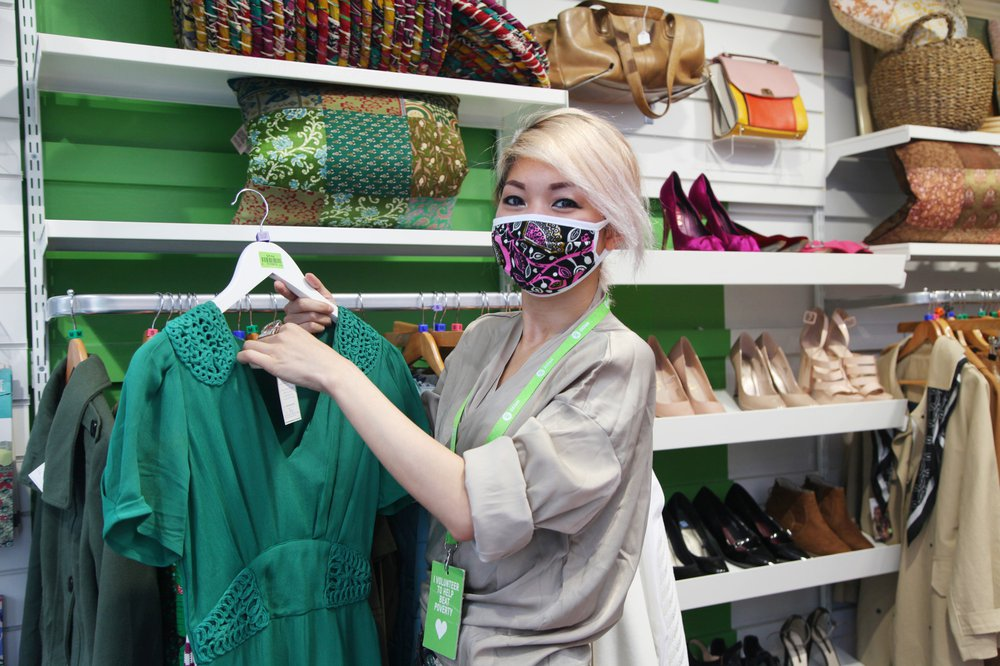 Shop volunteer Raphael Raphael Wong Hoi Ni is wearing a facemask in an Oxfam shop and holding a top by a clothes rail.