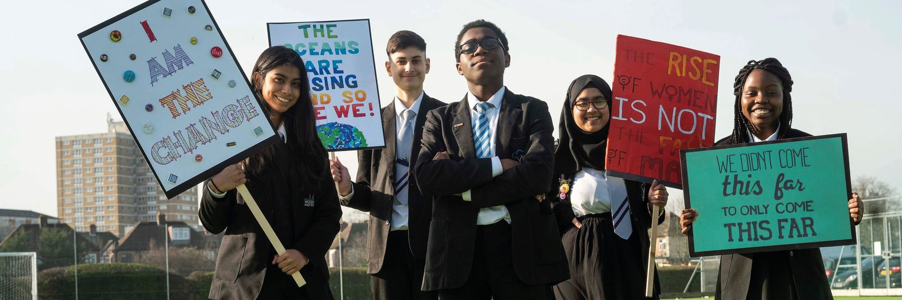 Pupils in blazers and ties from Woodside hold campaign banners