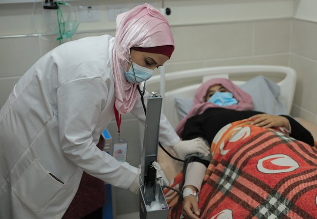 Nurse Heba Shalan is wearing a facemask and stethoscope and bending over a patient in a hospital bed who also wears a mask