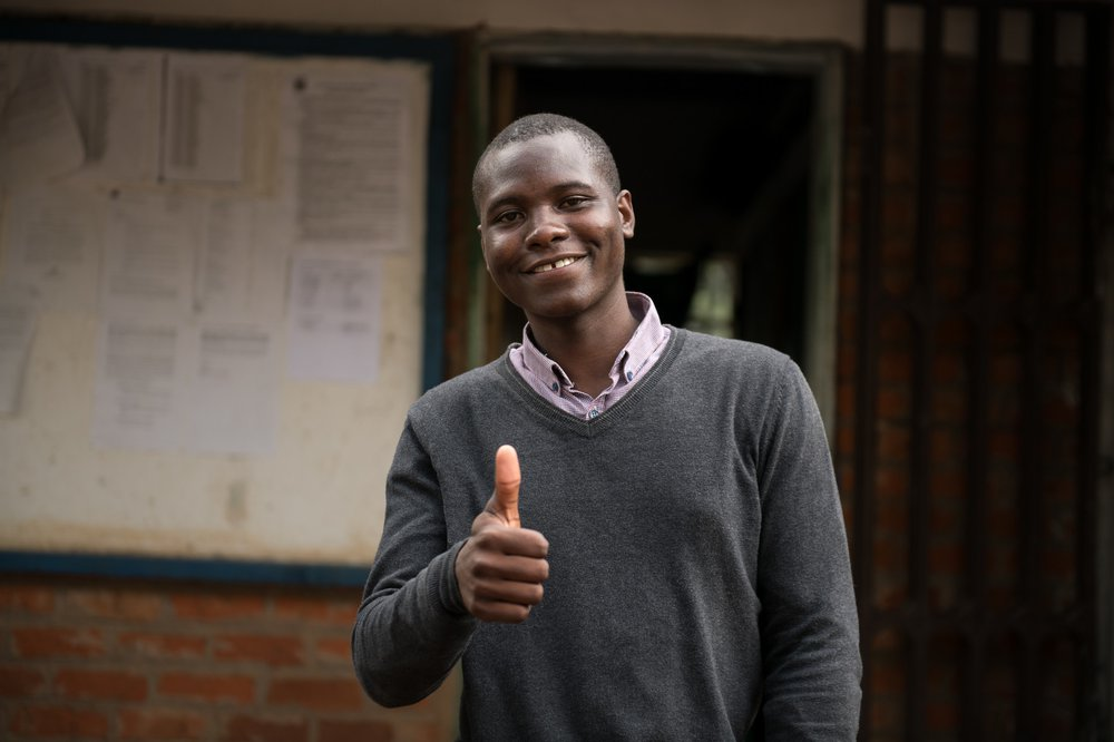 Isaac smiles and gives the thumbs up at home in Malawi