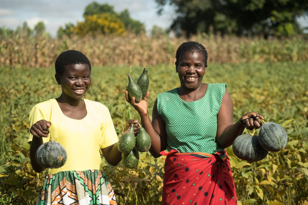 Jessy and her Mum stand in a field holding some crops they have grown and smile