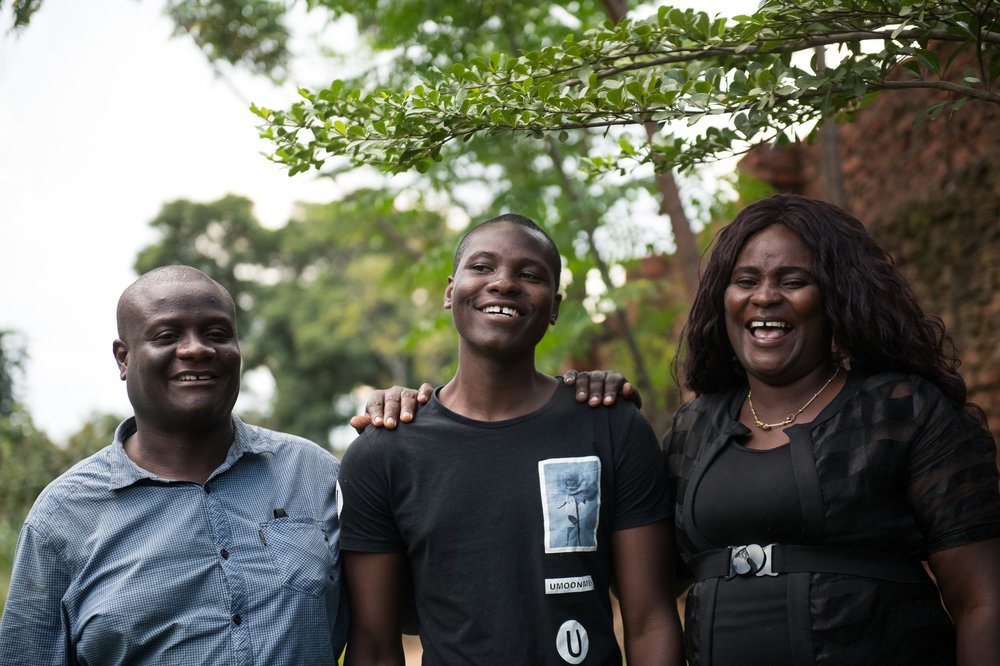 Isaac with his parents all laughing at home in Malawi