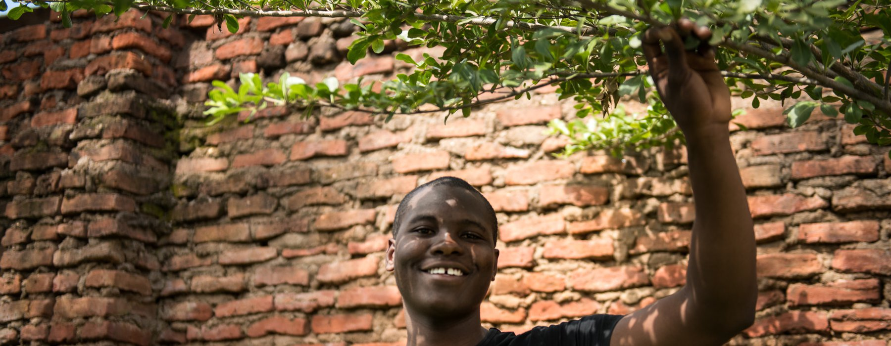 Isaac smiles and holds on to the branch of a tree by a red brick wall in Malawi