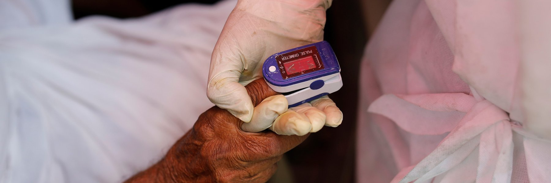 A volunteer's hand holds the hand of someone with Covid - their finger has an oxygen monitor on it