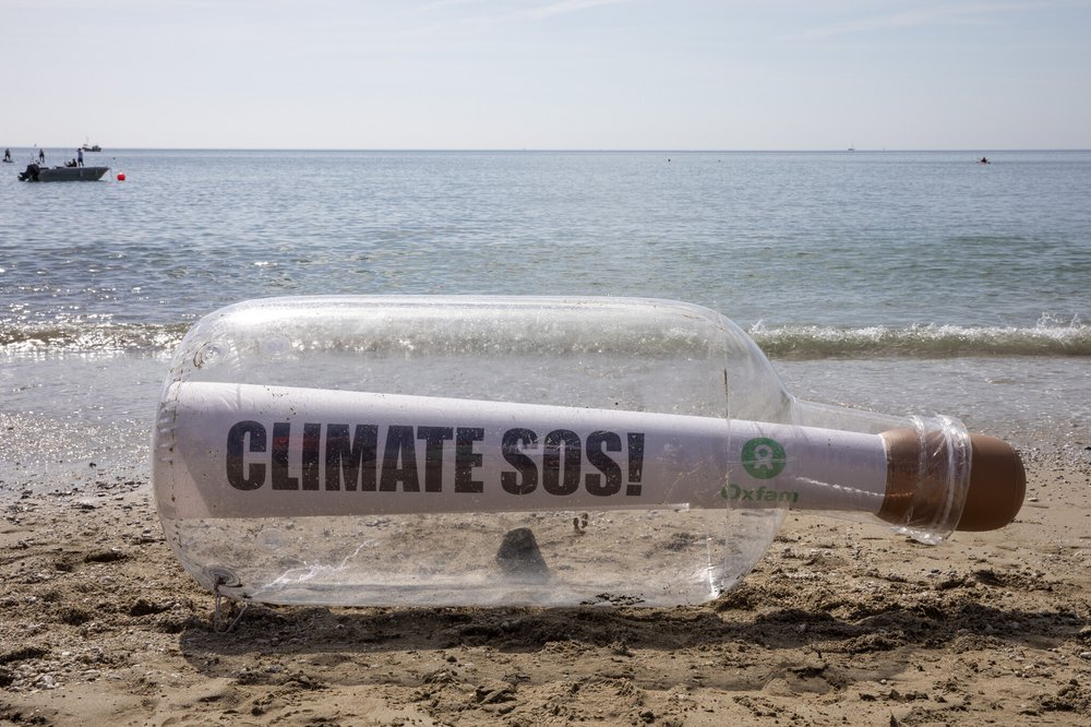 A giant bottle with a message that says Climate SOS and an Oxfam logo stit on the shoreline in Cornwall