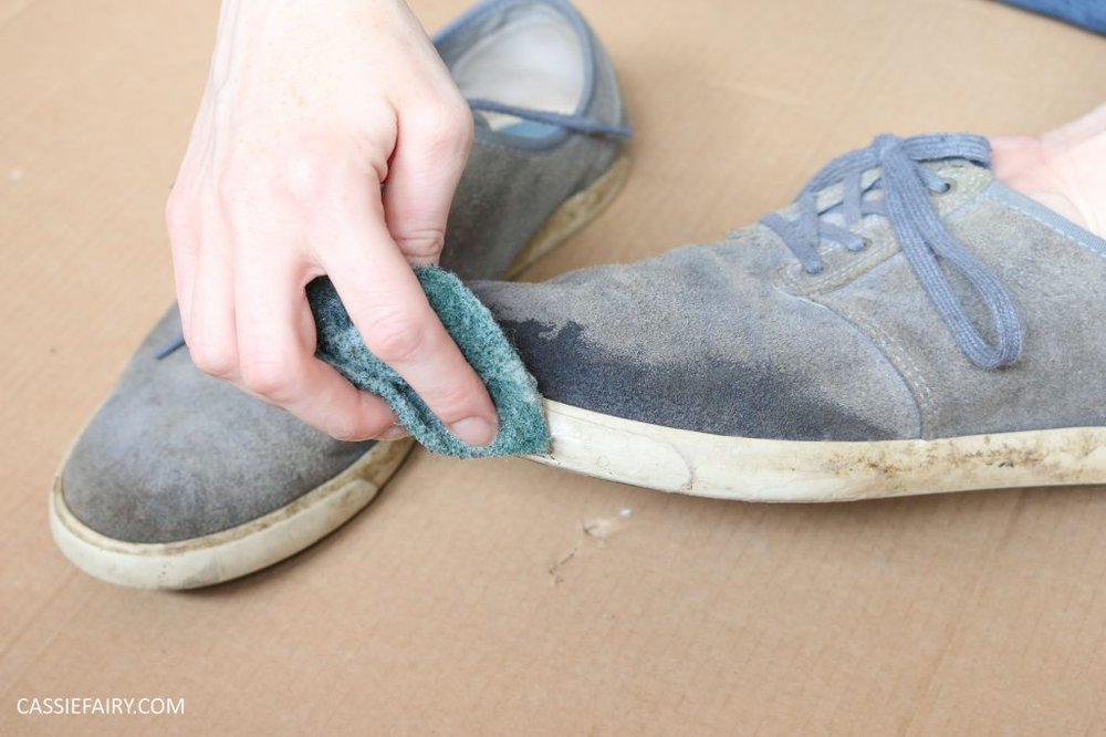 A pair of blue suede shoes being brushed with a cloth and then with a brush