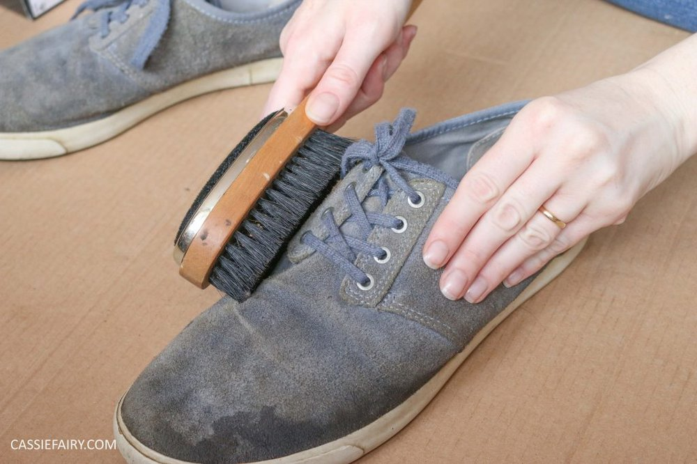 A pair of blue suede shoes being brushed with a brush