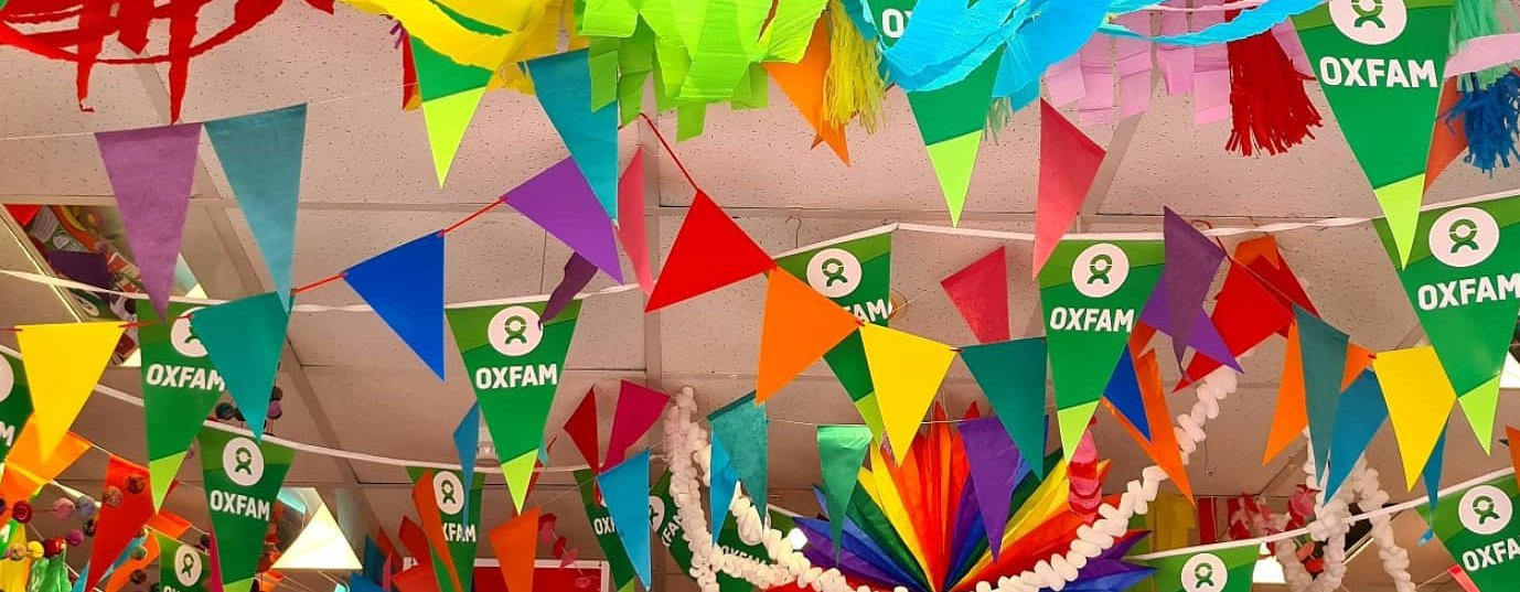 Inside the Oxfam Brighton shop during Pride month with loads of rainbow streamers and bunting