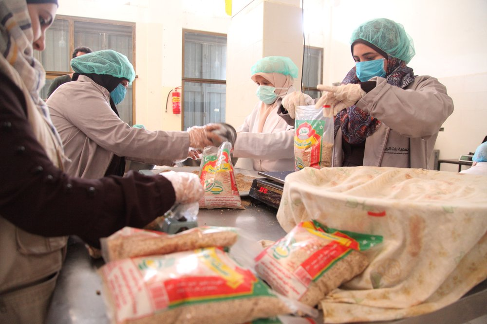 A group of women wearing blue hairnets and facemasks weigh and package food into plastic bags with green red and yellow on them.
