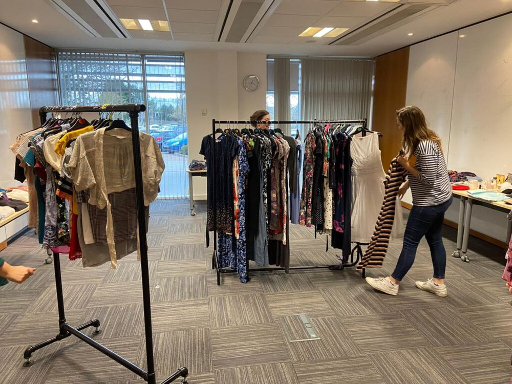 A women in a striped top stands looking at a row of second-hand clothes in a workplace swap shop
