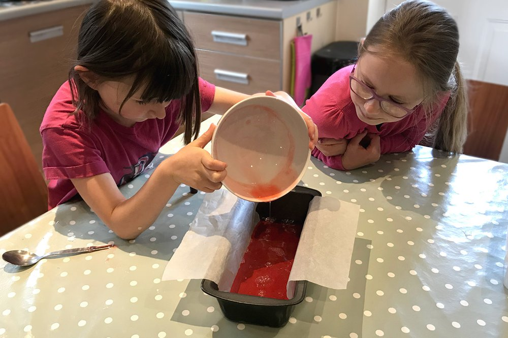 Two children look at a bowl of red liquid soap ingredients