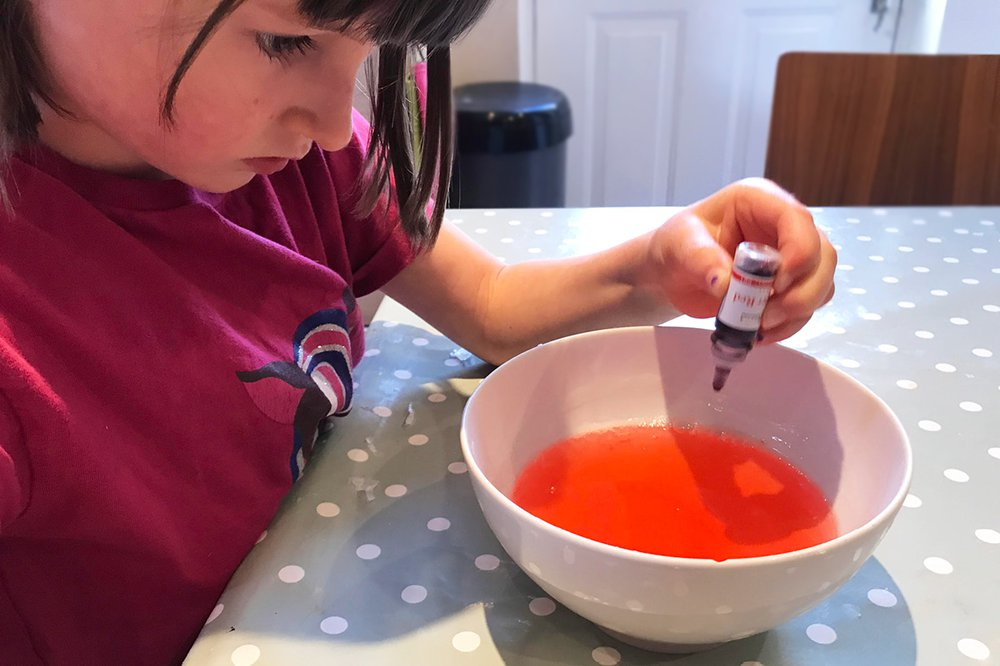 A girl uses a pippete to add colouring to glycerin