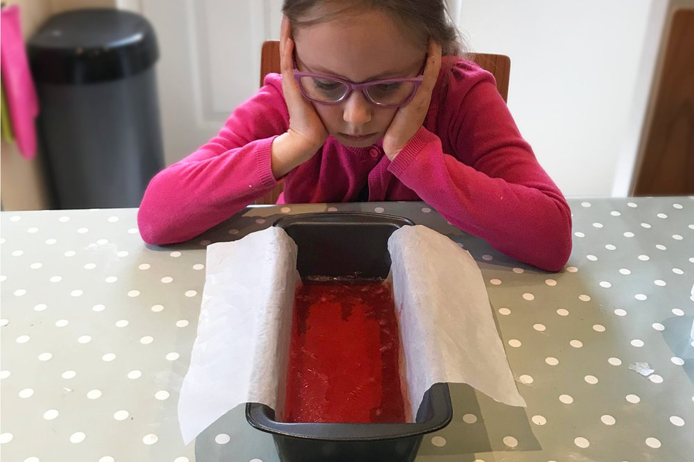 A child looks comically bored while waiting for homemade soap to set