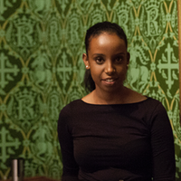 A profile picture of Sagal Ali with green wallpaper behind her