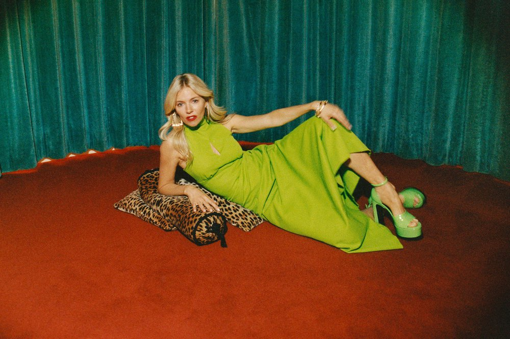 Sienna Miller sitting down with a knee up in a green dress and green heels