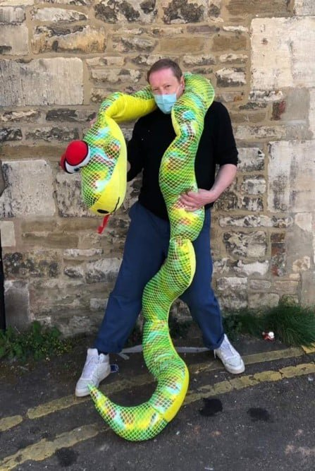 Shop staff member David with a giganitic green plush toy snake wrapped around him