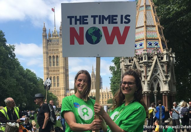 Two Oxfam staff members stand outside the Houses of Parliament holding up a placard saying 'The Time is Now'.