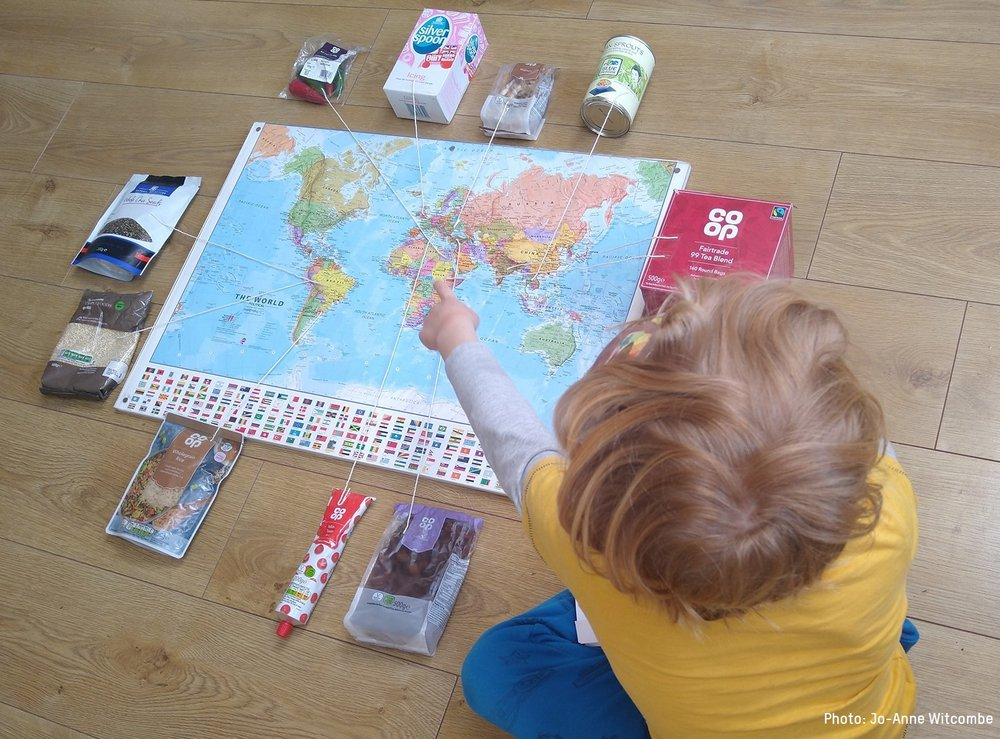A child looks at a map of the world with pins that strings to bags of real food from their family cupboard