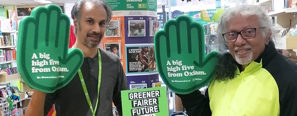 Vimal and Push in an Oxfam shop wearing green foam hands that say 'a big high five from Oxfam' with a 'greener, fairer future now' poster in the background.