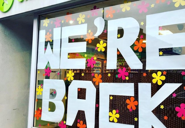 An Oxfam shop window with the words 'We're back' in white paper letters on it