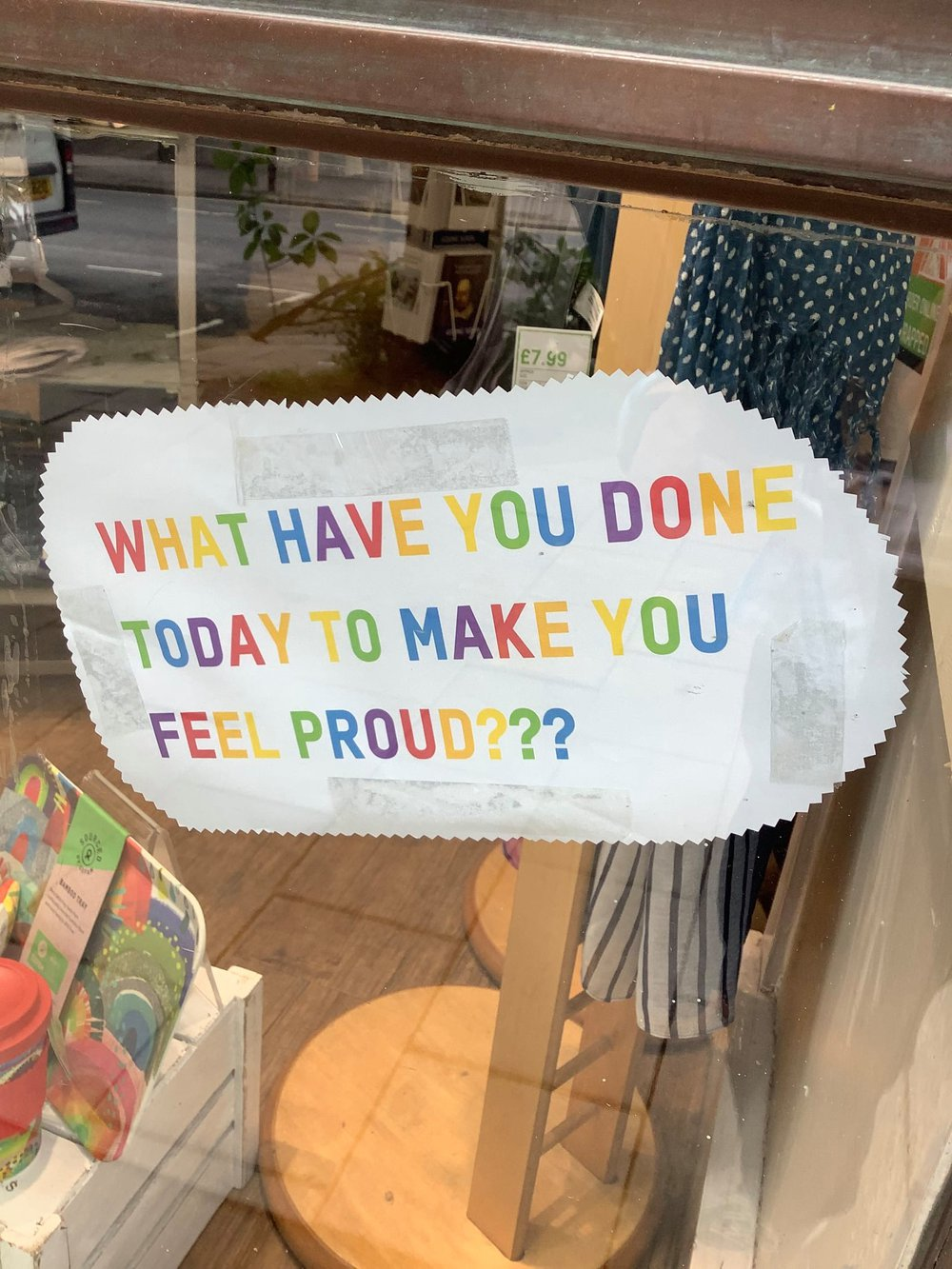 An Oxfam shop window with the words in rainbow colours 'what have you done today to make you feel proud'