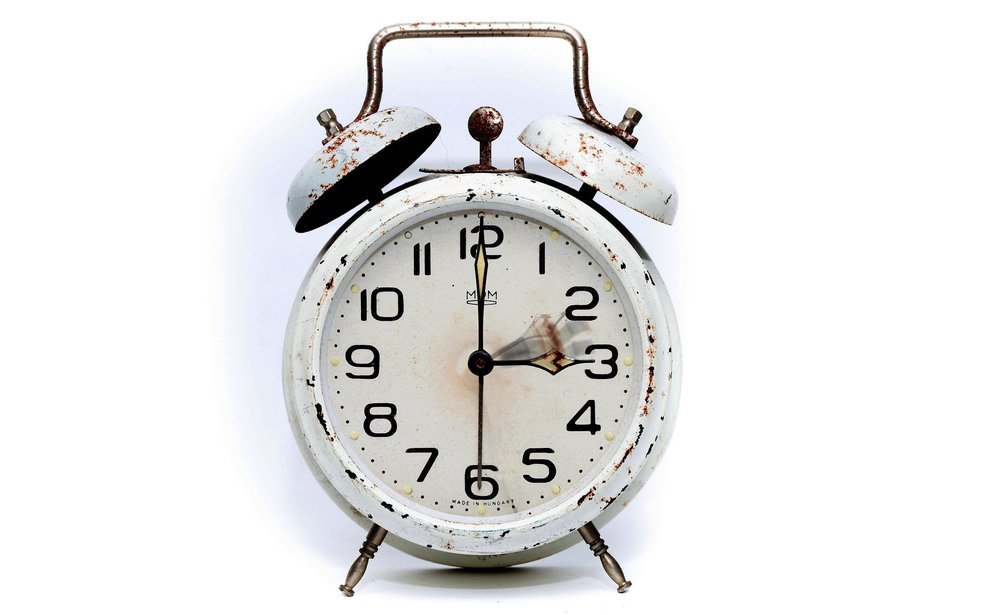 An old white alarm clock with patches of rust on it