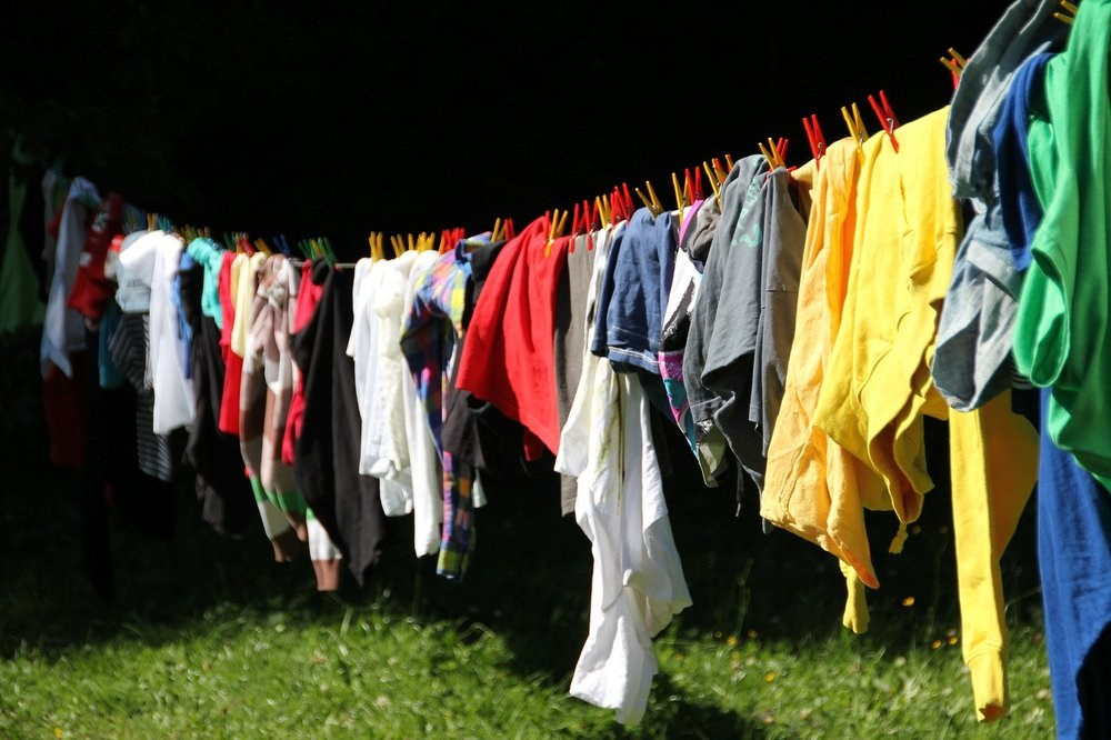 Colourful washing on a washing line above green grass.
