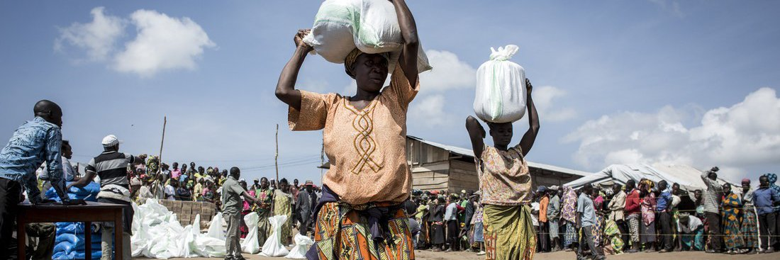 A woman collects a bag of dried food inside a camp in Bunia, DRC.