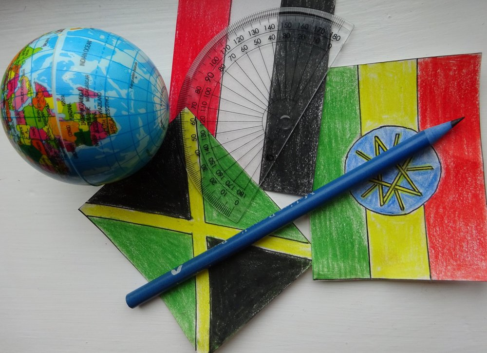 A protractor, pencil and some hand drawn pictures of flags.