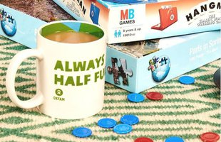 a selection of board games and a cup of tea with the message 'always half full' on