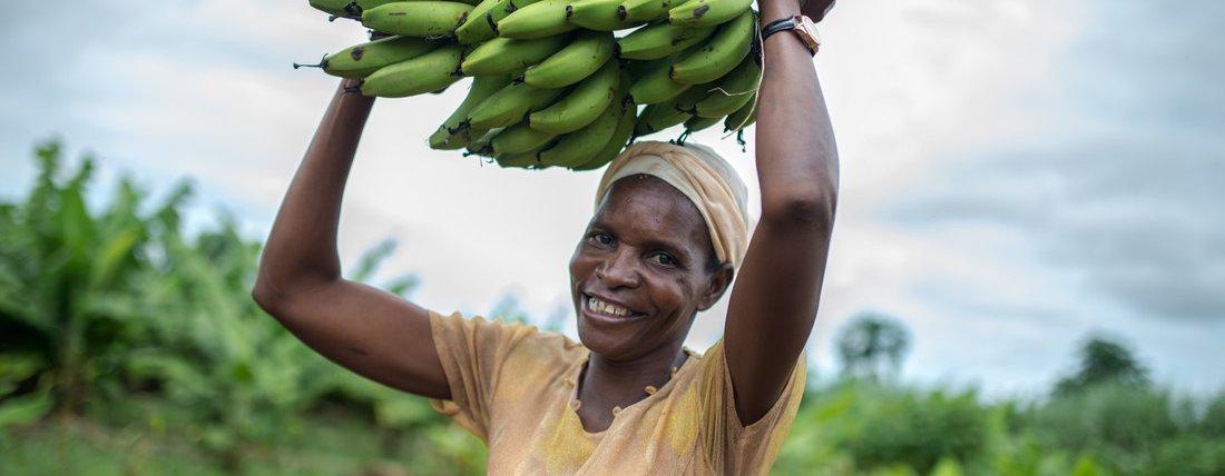 Idah, a member of the Kabwadu women's club, holds a bunch of bananas in Chirundu district, Zambia.