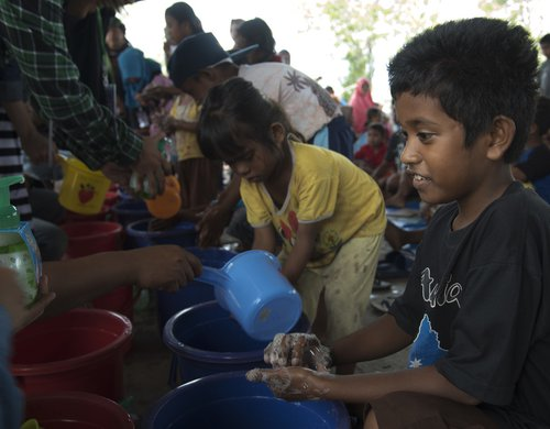 Children participate in a demonstration on good hygiene in the aftermath of a powerful earthquake.