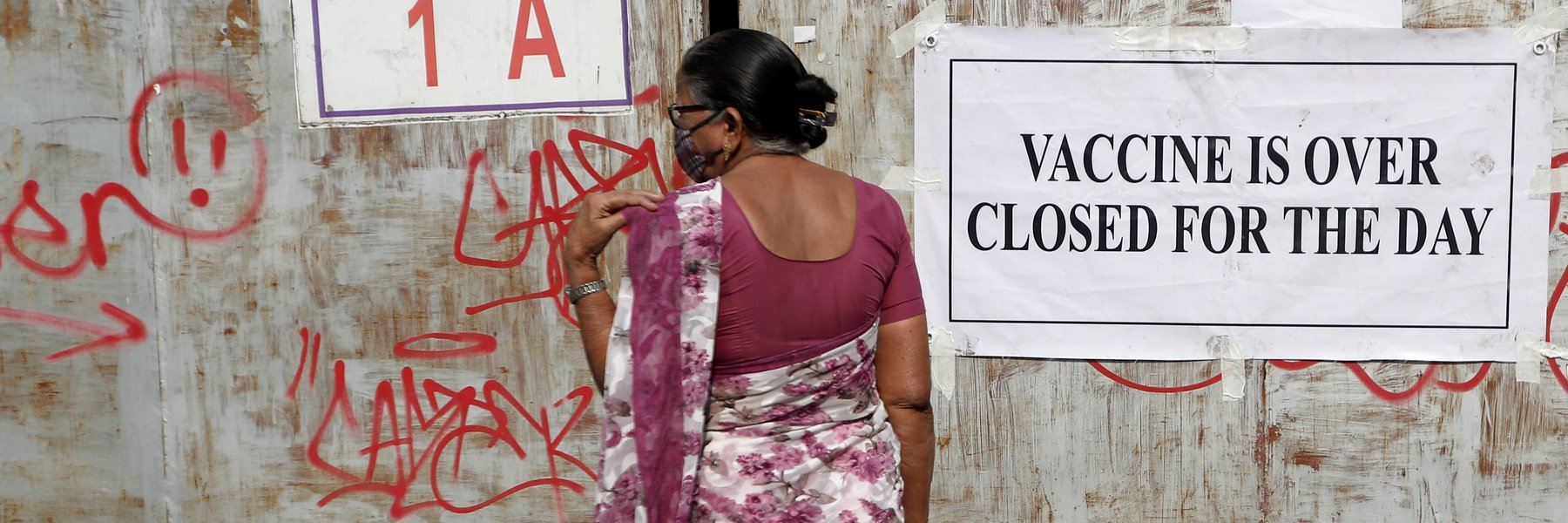 A woman stands in front of a closed gate of a vaccination centre which was closed due to unavailability of the supply of COVID-19 vaccine, in Mumbai, India. Photo: REUTERS/Francis M