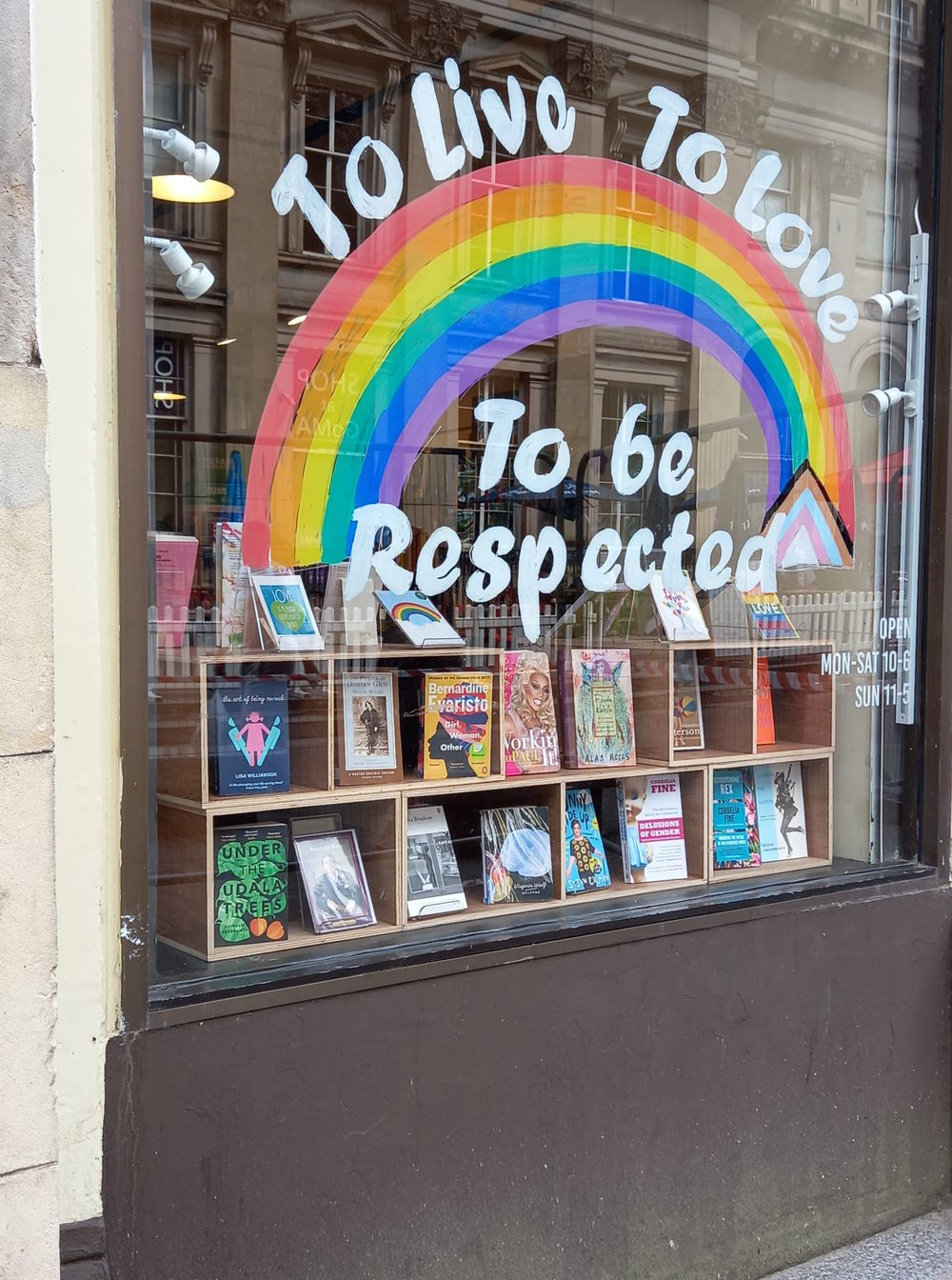 An Oxfam shop window with the words in rainbow colours 'live, love, be respected'