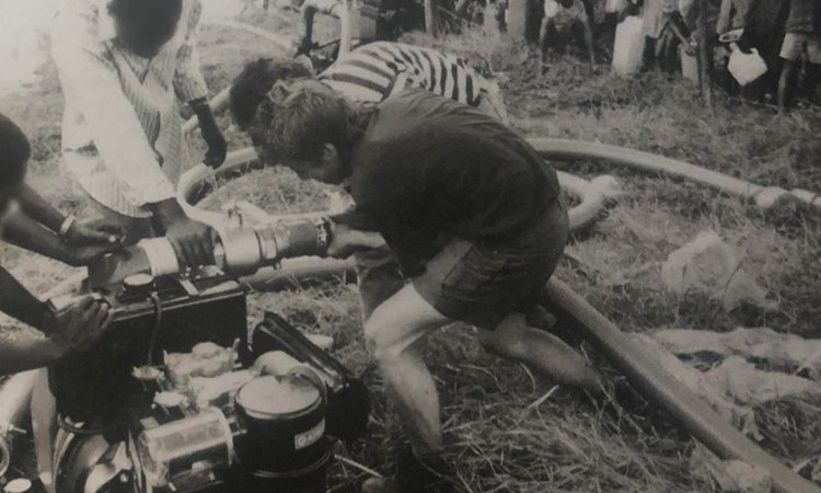 An Oxfam water engineer working with locals to install a pump in Ngara, Tanzania.