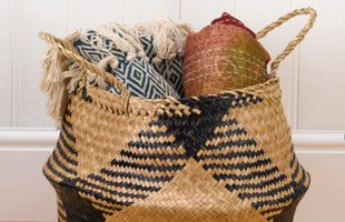 A seagrass basket filled with rolled blankets and rugs