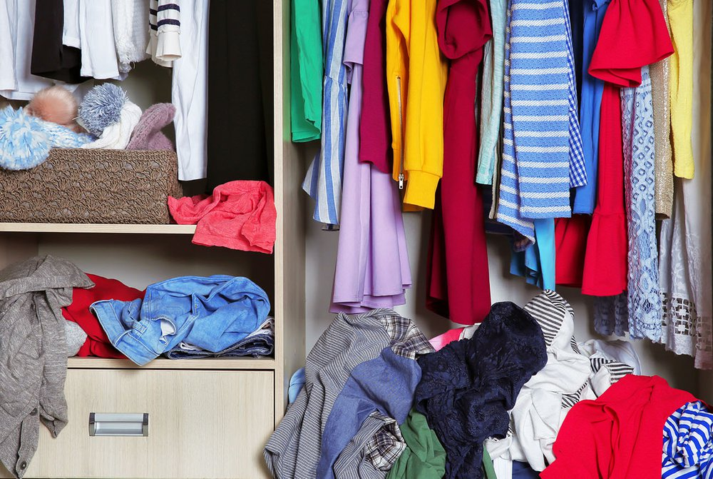 Clothes in a wardrobe and open drawers