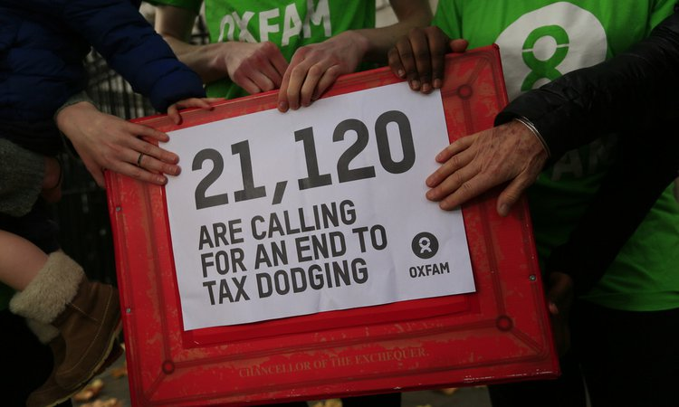Oxfam campaigners hand in a petition, calling on the Chancellor to introduce public country by country reporting to make corporation tax for UK businesses more transparent.