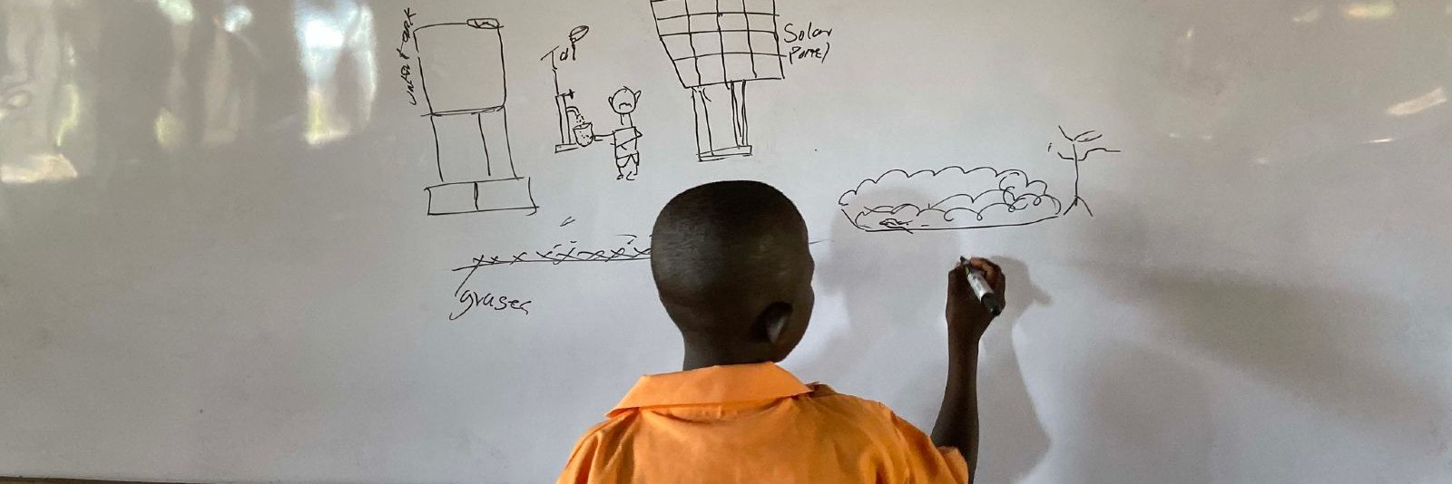 A student at a school in Ghana drawing a diagram of a solar pump. Oxfam installed a solar water pump in the community in 2019.